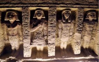 Four statues of people carved into the wall of the tomb