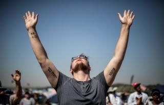 Followers of South African Christian revival evangelist Angus Buchan pray at an informal airfield outside Pretoria on October 27, 2018, for the 'It's Time' prayer, an event poised to become the Southern Africa's biggest ever prayer meeting...