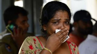 遇难者家属认领亲人遗体时,不禁掩脸落泪。
