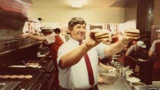 """Michael """"Jim"""" Delligatti con dos Big Mac en sus manos."""
