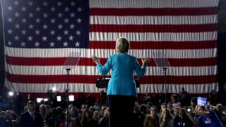 Hillary Clinton de espaldas sobre el escenario en un acto de campaña, 2016.