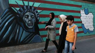 Iranians walk past anti-US graffiti in Tehran (file photo)