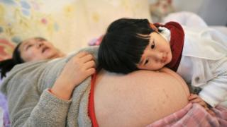 A woman, pregnant with her second child, lies on a bed as her daughter places her head on her mother's stomach in Hefei, Anhui province, China, in February 2014