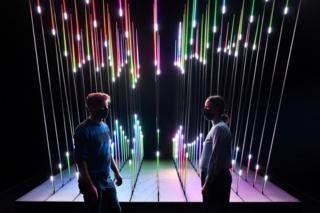 Two people wearing face masks stand in front of an illuminated, multicolour exhibit