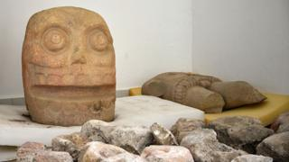 A large stone head and a torso of the God pictured on display