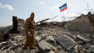 Чоловік у військовій формі і прапор ДНР