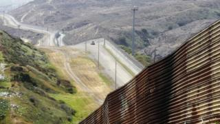 A stretch of wall runs along the US-Mexican border