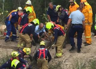 Australian man Daniel Miller is pulled from a dam by a fire and rescue team