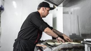 Cocinero tostando arepas en cocina fantasma.