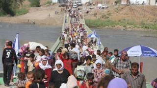 Displaced Yazidis cross the Syrian-Iraqi border along the Fishkhabur bridge in August 2014