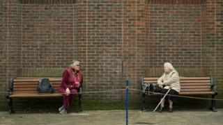Two women observe social distancing measures in York