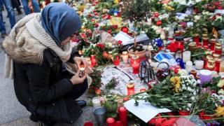 A young Muslim woman lights a candle outside the French Embassy in Berlin