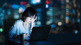 موظفة تعمل ليلا على جهاز كمبيوتر محمول