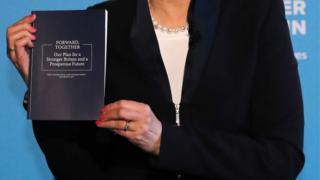 PM Theresa May holding manifesto