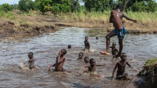 Boys take advantage of a river created by flash floods