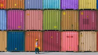 Trabalhador em frente a containeres