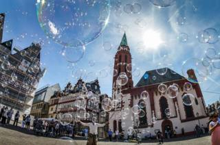A street artist makes soap bubbles in front of the Alte Nikolaikirche at the Roemerberg Square in Frankfurt, Germany on 12 August 2018.