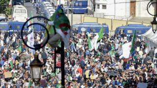 Algerians take part in an anti-government demonstration in the capital Algiers on November 1, 2019. - Demonstrators converged on Algiers in their thousands for a massive anti-government rally called to coincide with official celebrations of the anniversary of the war that won Algeria's independence from France.