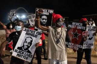 Activists raise their fists in Accra, Ghana on during the protest.