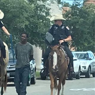 Two officers on horseback leading suspect on foot