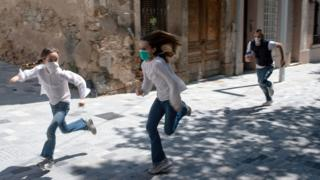 Joan, 45, chases his daughters Ines, 11, and Mar, 9, as they play in the street on April 26, 2020, in Barcelona, during a national lockdown to prevent the spread of the COVID-19 disease