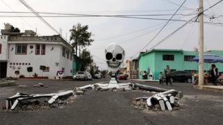 A cardboard skeleton emerges from a street in Mexico City