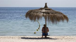 A tourist sits of the beach at the Riu Imperial Marhaba Hotel in Port el Kantaoui, on the outskirts of Sousse south of the capital Tunis, on June 29, 2015