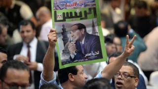 رجل يحمل صحيفة تعلن فوز عبدالفتاح السيسي بالانتخابات، في الثاني من أبريل/نيسان 2018