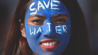 Женщина на демонстрации за снижение расходов воды