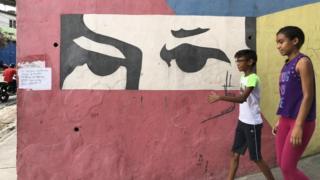 Dos niños frente a un mural en Venezuela