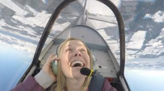 Woman in plane looping-the-loop over the Black Isle.