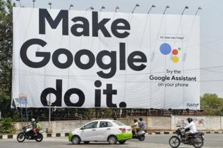 Indian commuters drive past an advertisement poster of Google in Bangalore on 6 April 2018.