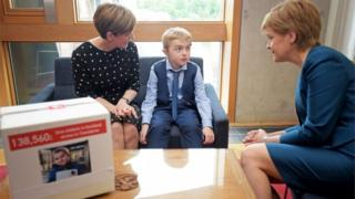 Michael Young, his mother Michelle and the first minister