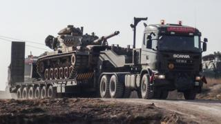 A photo made available by the Dogan New Agency shows Turkish military trucks transporting a tank to the border with Syria near Sanilurfa on 16 January 2018