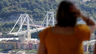 A woman looks at Genoa's shattered bridge. 16 August