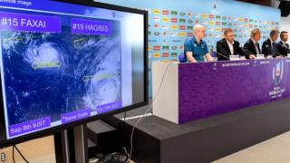 Rugby World Cup organisers brief the media as a screen shows the path of the approaching typhoon