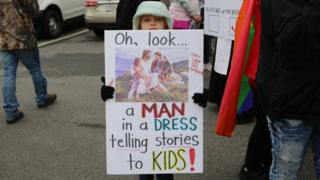 A child holding a sign in support of the drag queen story hour event