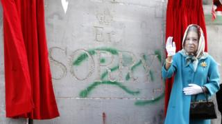 "An actor dressed as Queen Elizabeth II in front of a mock apology for the Balfour Declaration etched into Israel's West Bank barrier that says: ""Er... Sorry."""