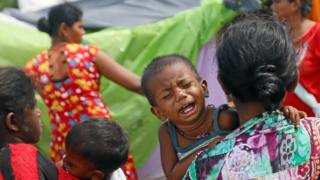 A boy who lives in a temporary shelter cries as his mother walks along a street near a flood affected area in Kelaniya