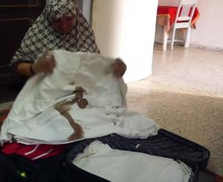 Sayeda weeps into bloodied sheet taken from her suitcase