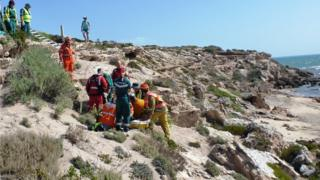 A rescue crew helps the woman after she broke her leg