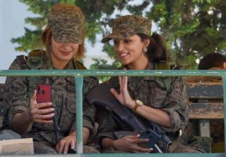 Two female officers in army fatigue are seen on a vehicle, smiling as they take a selfie.