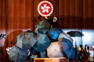 in_pictures A protester defaces the Hong Kong emblem after protesters broke into the government headquarters in Hong Kong on 1 July 2019, on the 22nd anniversary of the city's handover from Britain to China