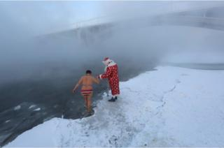 A man dressed as Ded Moroz, the Russian equivalent of Santa Claus, helps a member of the Cryophile amateur winter swimmers club into the icy waters of the Yenisei River in Krasnoyarsk, Russia, 30 December 2018.
