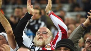 Man wearing Sunderland and Newcastle shirt
