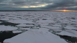 A view over the Weddell Sea, covered in white ice pack. The clouds are low and grey and the sun sets on the horizon