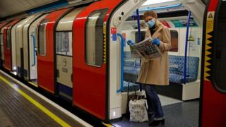A woman wearing PPE (personal protective equipment), including a face mask as a precautionary measure against COVID-19, reads a newspaper as she stands aboard a London Underground Tube train, i