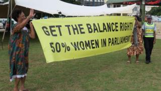 Mulheres segurando um cartaz com mensagem em inglês exigindo representação igualitária no parlamento de Vanuatu