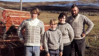 A family of Shetlanders pose wearing Fair Isle jumpers in front of lobster pots on one of the Shetland Islands in 1970.