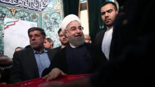 Mr Rouhani (na tsakiya) ya kada kuri'arsa a Tehran, babban birnin kasar.